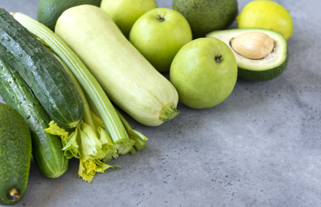 fruits and vegetables on a gray background, apples, cucumbers ,zucchini, avocado, lime, celery, healthy food