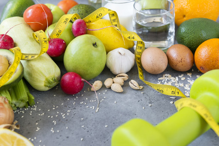fruits and vegetables, eggs ,glass of water, dumbbell, measuring tape on gray surface, health food, apples, radishes, zucchini, garlic, lemon, avocado Reklamní fotografie - 122781236