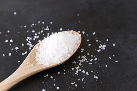 white coarse salt on a light wooden spoon on a black surface