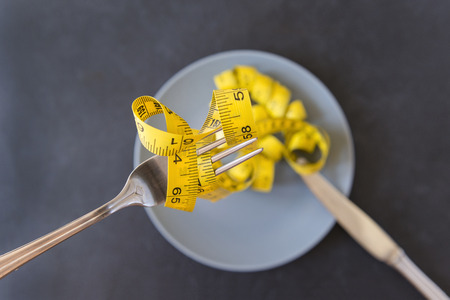 yellow measuring tape on fork and grey plate, knife, diet Reklamní fotografie - 122781279