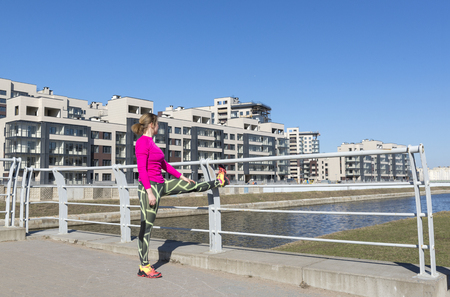 white girl in sporty pink top and leggings doing leg stretching outside on a Sunny day ,at home along the canal embankment, young woman doing outdoor sports Reklamní fotografie