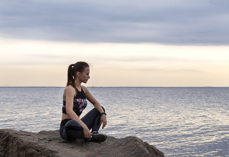 white slender beautiful girl with long hair in sportswear sitting on a rock by the sea at sunset Reklamní fotografie - 122781286