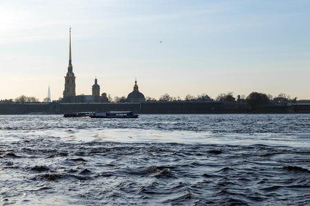 view of the Neva river and Peter and Paul fortress and the Orthodox Cathedral at sunset, a pleasure boat on the river in St. Petersburg Reklamní fotografie - 122781282