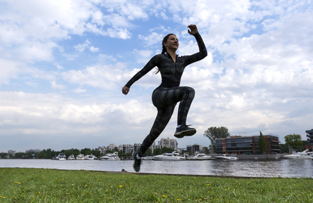 1 white girl in sports clothes running in the Park on the river Bank against the sky with clouds , runner, athlete Reklamní fotografie - 123667635