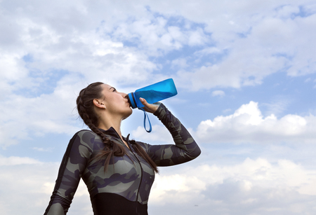1 white slender girl in sports clothes drinking water from a bottle against the sky with clouds ,athlete Reklamní fotografie