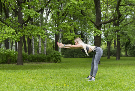 1 white slender girl goes in for sports in the Park, she does the forward bends, Reklamní fotografie - 123667639