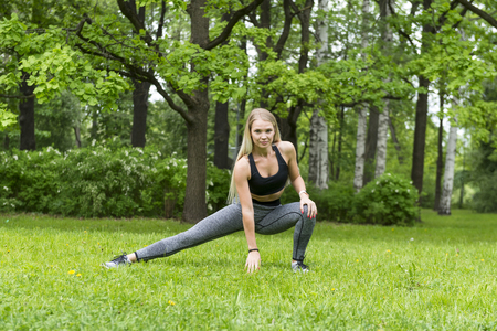 1 white slender blonde girl in sports top and leggings doing sports in the Park among the green trees Reklamní fotografie