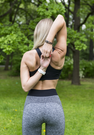 slender blonde girl from the back, a girl in sports clothes holds her hands in the castle behind her , training in the Park among the greenery Reklamní fotografie - 123667641