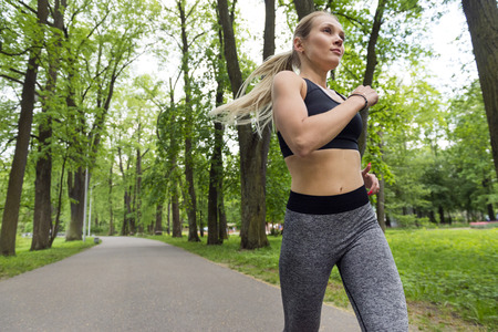 1 white slim athletic girl running on a track in a Park among green trees, runner, Reklamní fotografie