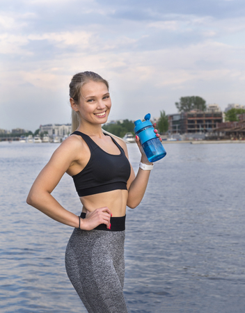 slender athletic girl in sports clothes with a bottle of water in hands stands on the river Bank against the sky at sunset, the blonde girl smiles