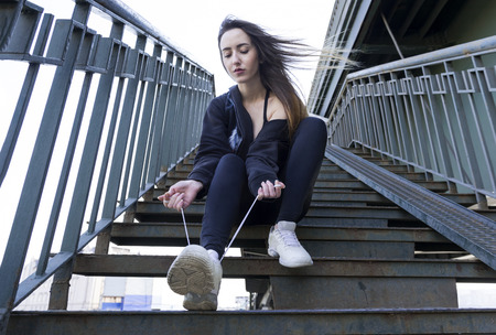 1 white beautiful girl with long hair and black clothes sitting on the stairs and tying her shoelaces Reklamní fotografie