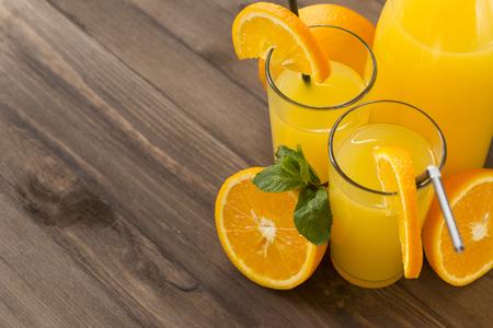 orange juice glass with mint on brown wooden background, orange, juice bottle Reklamní fotografie