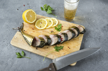 pieces of smoked mackerel with spices on the cutting Board, knife, smoked fish , lemon, glass of light beer Reklamní fotografie