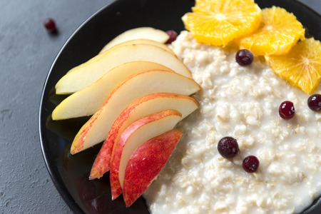 porridge with pieces of pear, orange, cranberry, oatmeal with berries and fruits