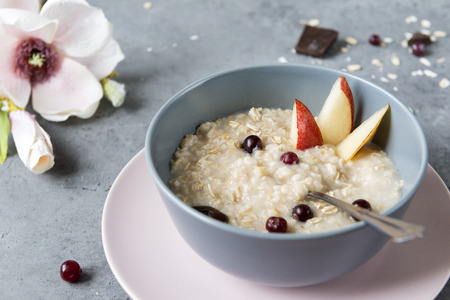 plate of oatmeal with berries and fruits on a gray background, porridge with cranberries and pears, Magnolia flower, Breakfast Reklamní fotografie