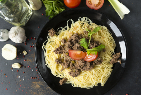 black plate of Italian pasta with meat sauce, tomato and herbs, spices on black background