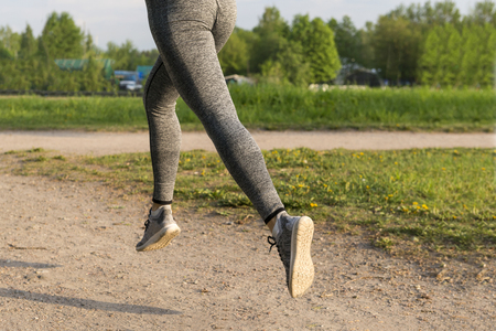 runner, girl running in the Park, womens feet in gray leggings and sneakers on the path in the Park in the sun,
