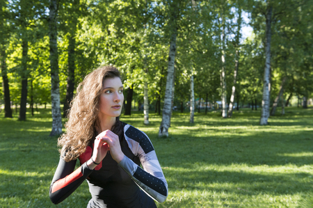 beautiful slender girl with long wavy hair doing sports in the Park against the background of greenery