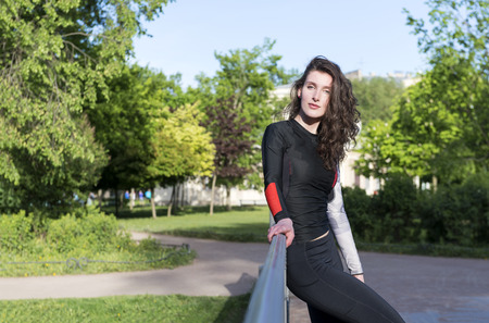 1 white slender beautiful brunette girl with long wavy hair in sportswear stands against the trees and smiles slightly Reklamní fotografie
