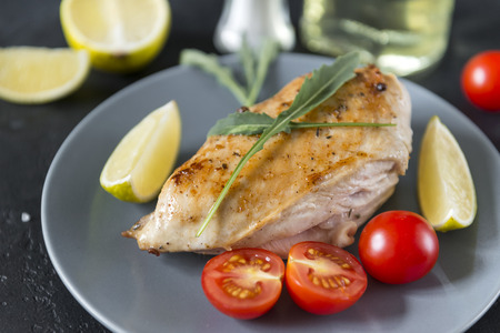 grilled chicken breast with arugula, tomatoes and a slice of lime on a gray plate on a black background