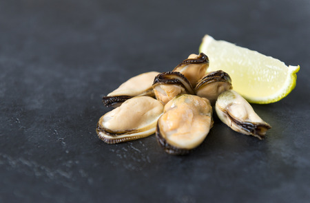 several marinated mussels with a slice of lime on a black background, seafood, shellfish,