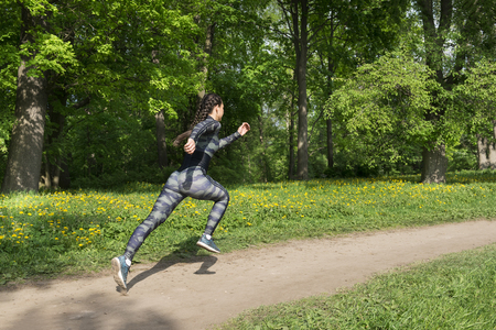 1 white brunette girl with pigtails in khaki sportswear and sneakers runs fast through the Park among the greenery Reklamní fotografie