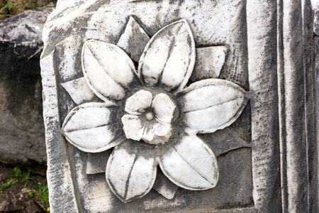stone flower, flower engraved on marble stone, antique stone block, Reklamní fotografie