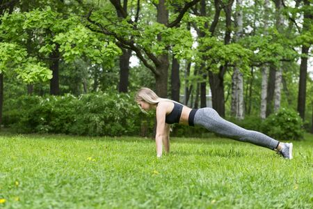1 white slim athletic blonde girl with long hair doing sports in the Park among the trees