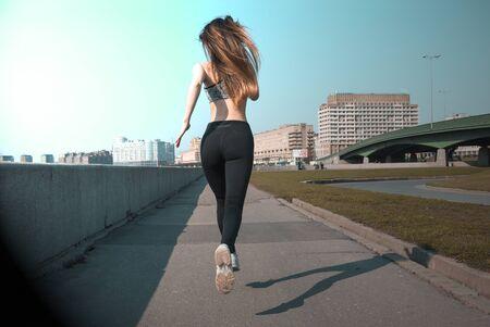 1 white slender girl with long hair running down the street in the city on a Sunny day, runner, Reklamní fotografie