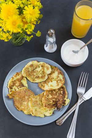 vegetable pancakes on a plate, zucchini pancakes, sour cream, a glass of orange juice, a bouquet of yellow dandelions, a fork with a knife, top view