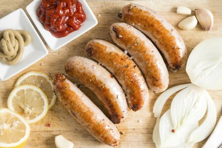 meat fried sausages with onion, lemon, garlic, ketchup and mustard on wooden cutting Board