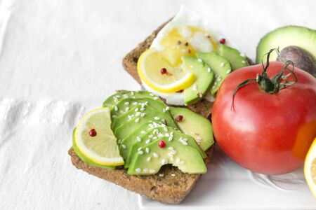 sandwich with pieces of avocado and lemon, sesame, next to a red tomato on a white tablecloth Reklamní fotografie