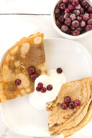 pancakes with sour cream and berries on a plate, pancakes with cranberries, cranberries in a plate