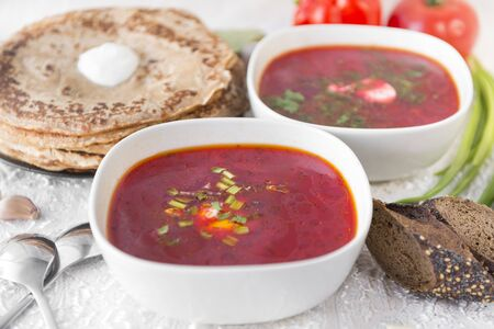 2 plates of red Ukrainian borsch, soup, plate with pancakes, a piece of bread, vegetables