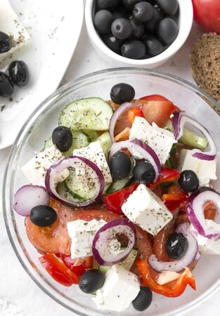 Greek rustic vegetable salad with feta and olives, tomatoes, cucumbers, onions and sweet pepper