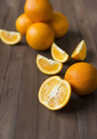lots of fresh juicy oranges on a brown wooden background, whole orange, half and orange slices Reklamní fotografie