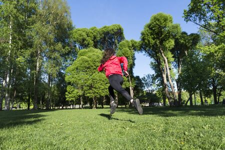 running,  girl in black leggings and a red jacket running across a clearing on a background of green trees and blue sky,  runner in the Park Reklamní fotografie