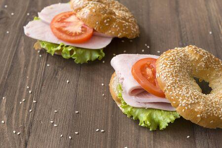 2 sandwiches on wooden background, ham , tomato, green lettuce leaf on round sesame bun, Reklamní fotografie
