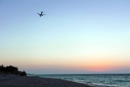 plane in the evening sky comes to land over the sea coast at sunset,  Mediterranean sea, Greece