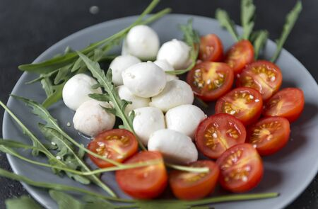 mozzarella balls with cut in half cherry tomatoes and arugula on a plate on a dark background