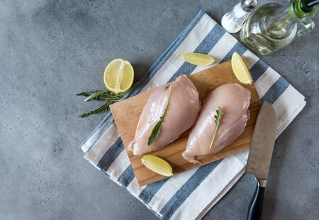 raw chicken fillet with arugula on cutting Board and towel ,knife, oil bottle and salt shaker on grey background, top view,