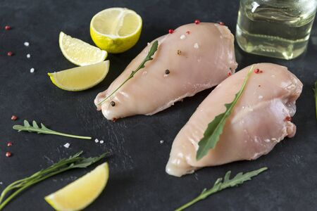 2 pieces of raw chicken fillet with arugula and spices on a black background, bottles of oil, slices of lime, Reklamní fotografie