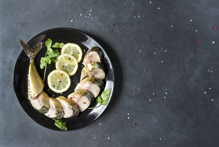 smoked mackerel cut into pieces with slices of lemon and herbs on a plate on a black background, top view