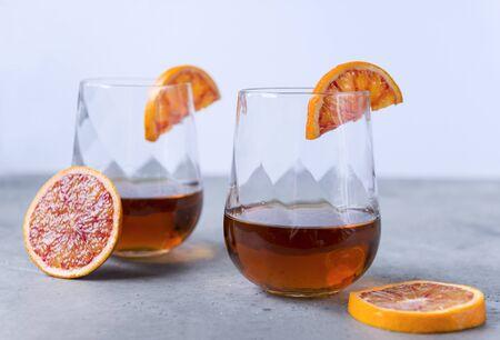2 glasses of cognac, slices of red orange on a gray background , strong alcoholic drink Reklamní fotografie