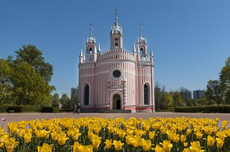 Orthodox Church of the Nativity of St. John against the sky on a Sunny day in St. Petersburg, flowerbed with yellow tulips