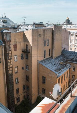 old buildings with Windows in the center of St. Petersburg, St. Petersburg courtyard, the dome of St. Isaacs Cathedral on the horizon against the sky