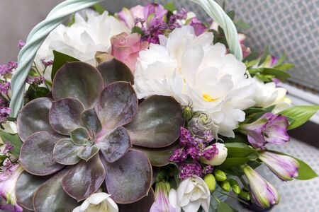 white peonies and pink roses, basket with a bouquet of flowers with succulenta,