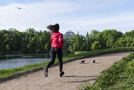 slender girl in black leggings and red jacket runs along the path along the pond in the Park