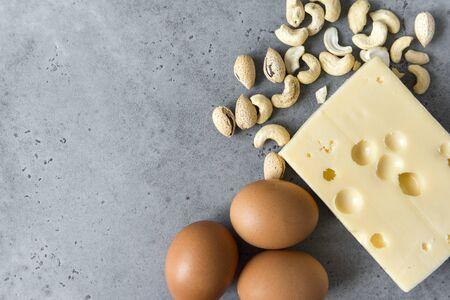 3 raw eggs, cashew nuts, Maasdam cheese,  on grey concrete background  Reklamní fotografie