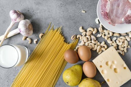 raw eggs, Maasdam cheese, cashew nuts, glass of milk, pasta , pears, piece of raw pork, meat, garlic on a gray background, healthy protein food Reklamní fotografie